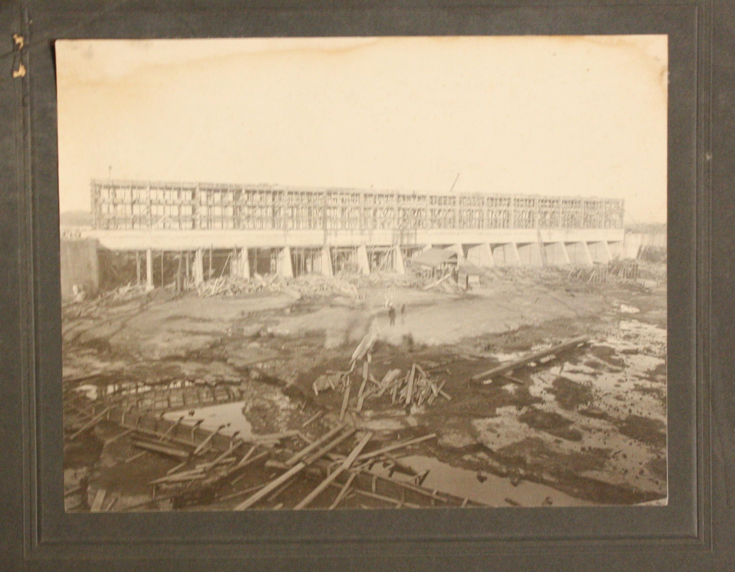 Black and white image from 1904 of the construction of the forebays of the Ontario Power Company. Large construction site, 16 rectangular intakes span the length of the forebay, scaffolding above these intakes. Two people are in the centre of the image; they are blurry due to the exposure time of the camera. The intakes are each about 20 foot by 20 foot.
