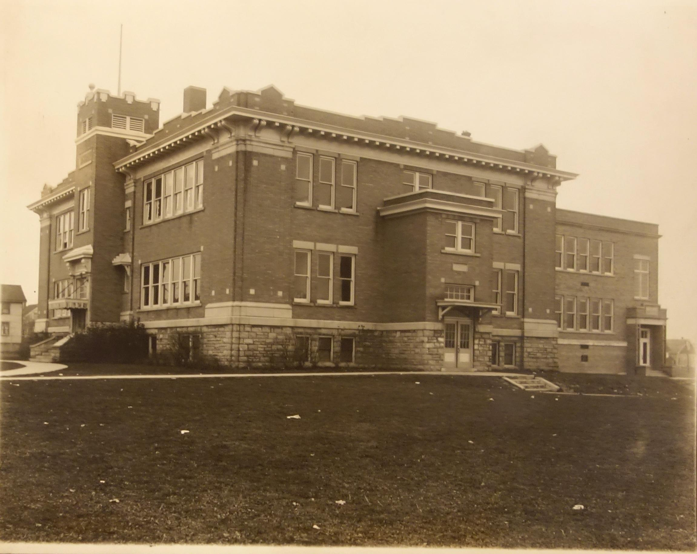 Niagara Falls Memorial School. Black and white photo showing a large brick school building with a flat roof, stone base and stone highlights. There is a tower on the left side of the image marking the entrance to the school. Many small windows are located along the side facing the photographer.  Decorative battlements surround the roof. There is a concrete sidewalk stretching about the school building with the grass school yard.