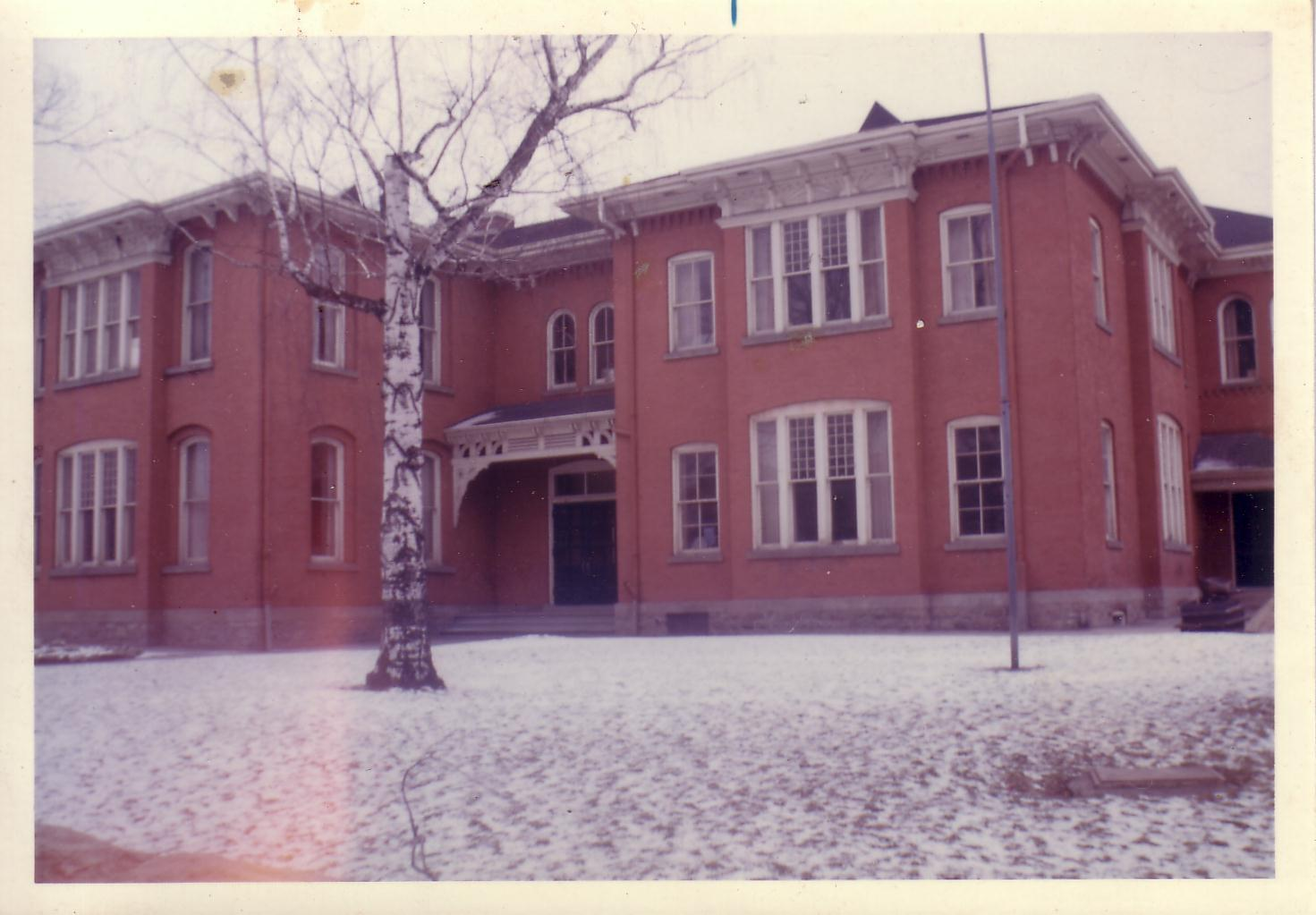 Simcoe Street School. Colour photograph, showing brick schoolhouse with a stone base. Hip roof with elaborate cornices and corbels along the projection of the roof. There are large windows with a slight arch. A willow tree stands in front of the building, no leaves as the photo was taken during the winter; snow is on the ground.
