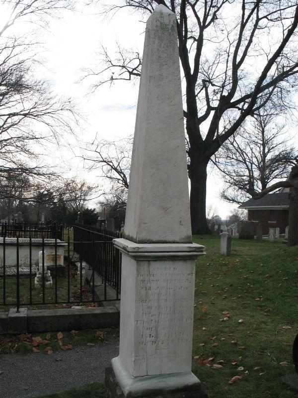 Edgeworth Ussher's Grave Marker. White monument, square base, stands about 8 foot tall. An obelisk design, which means that it comes together to a point at the top, forming a triangle; these were popular in the neo-classical period of the 19th century due to findings in Egypt. It was taken in Drummond Hill Cemetery, there is a grounds-keeping building in the background of the image.