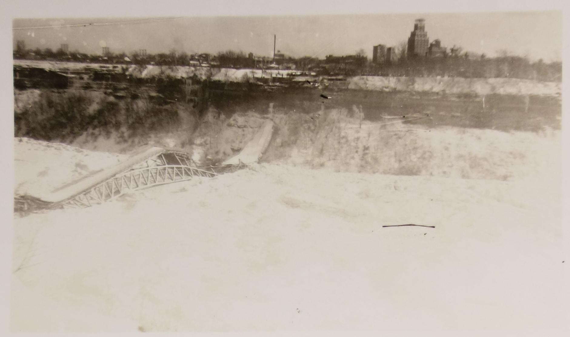 Collapsed Honeymoon Bridge (January,1938) The Honeymoon Bridge laying on the ice bridge which caused it to collapse. Black and white photograph. Steel structure beneath bridge with snow covered wooden surface; the bridge collapsed with a rise in the middle. Niagara Falls, New York in the background of the photo.