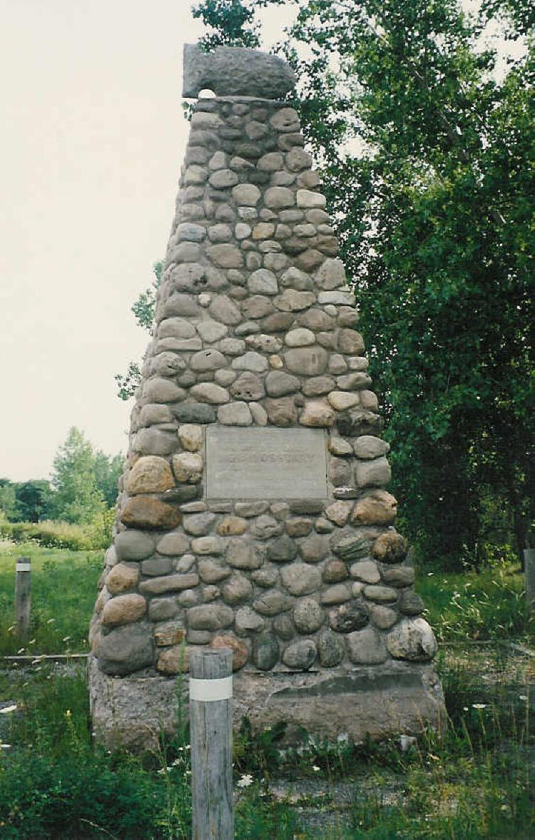 Coloured photograph of the Cairn which stands at the site of the Indian Ossuary. The large stone structure is held together with cement. A large stone