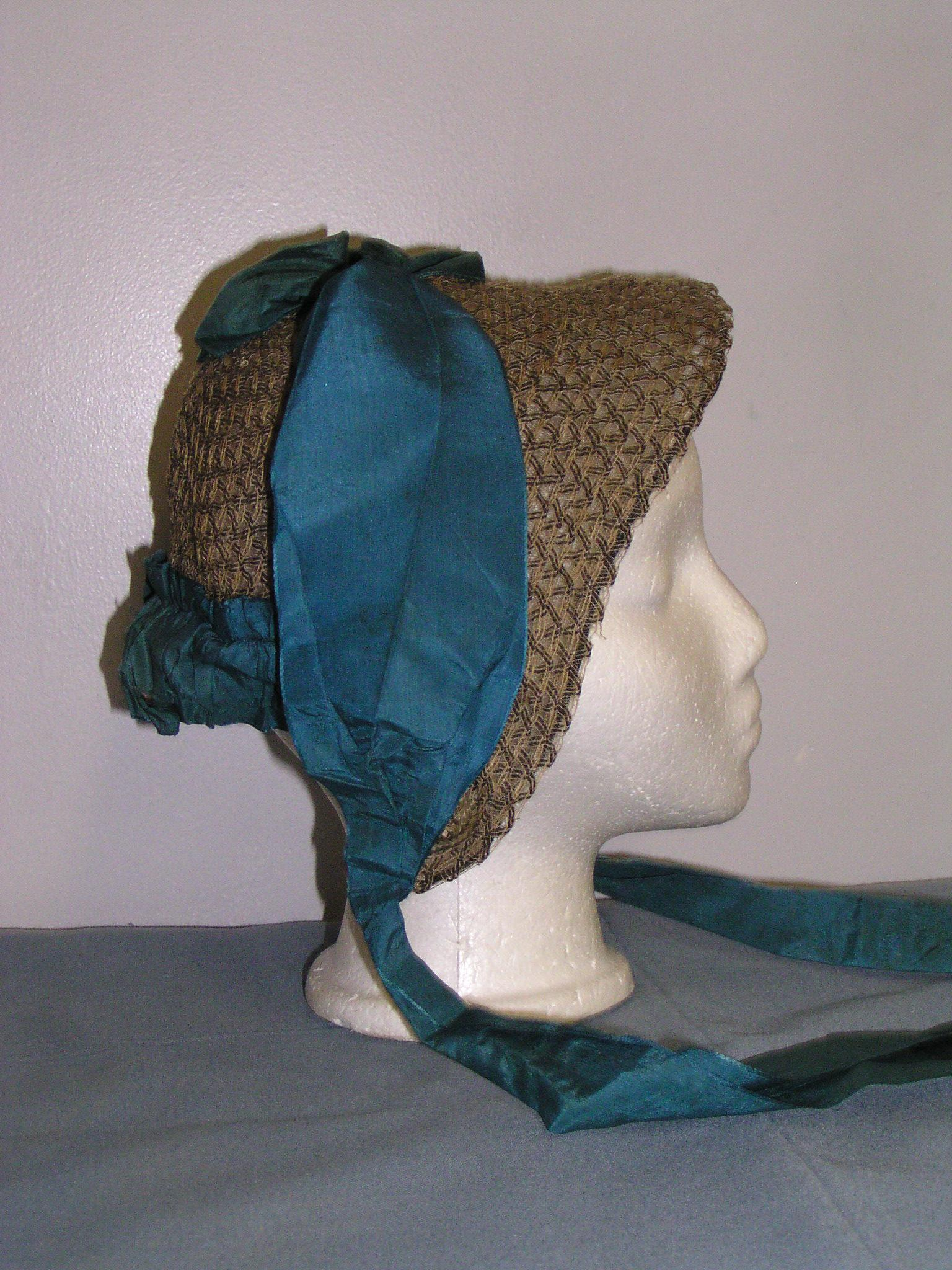 Laura Secord's straw bonnet with a long and thick blue ribbon around the crest of the bill to the back of the hat and ties extending past the bonnet with which the bonnet is tied in highwinds. It is placed on a white mannequin head with a grey background and grey table. The weaving of the hat is intricate forming chevorns pointing toward the face.