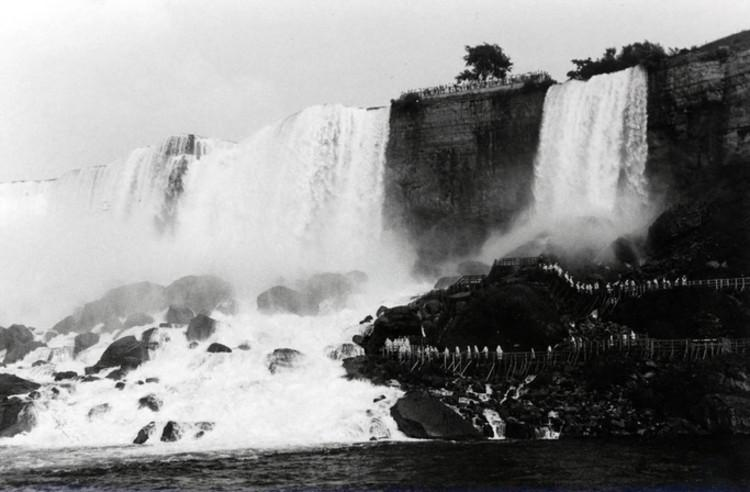 Image courtesy of the Niagara Falls (Ontario) Public Library. Black and white photograph of the American Falls, with the Cave of the Winds mid-way down the right side. The American Falls, on the left, dwarf the Luna Falls (or Bridal Veil Falls) on the right. Large boulders rest at the bottom of both falls, creating rapids and halving the height of both falls. A single tree stands on Luna Island, which is an island between the American and Luna Falls.