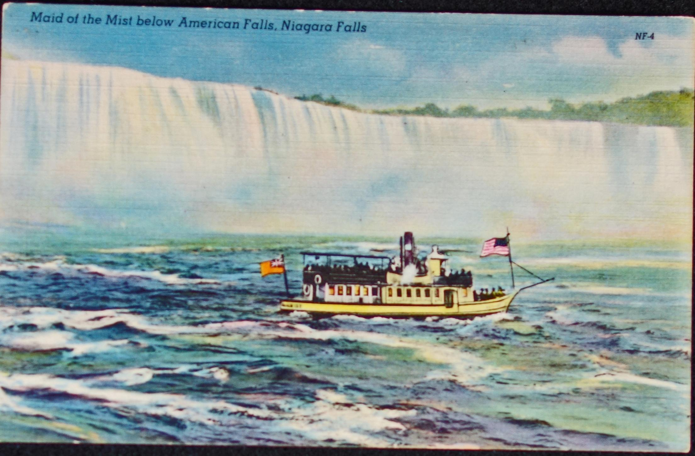 Colourised postcard of the Maid of the Mist in the Niagara River in front of the American Falls; Bridal Veil falls appears at right of the photo. A line of trees are shown as wel above the water on the right half of the photograph. On the bow is the American flag and at aft is a Red Ensign. Chimney for steam power is at the middle of the boat.