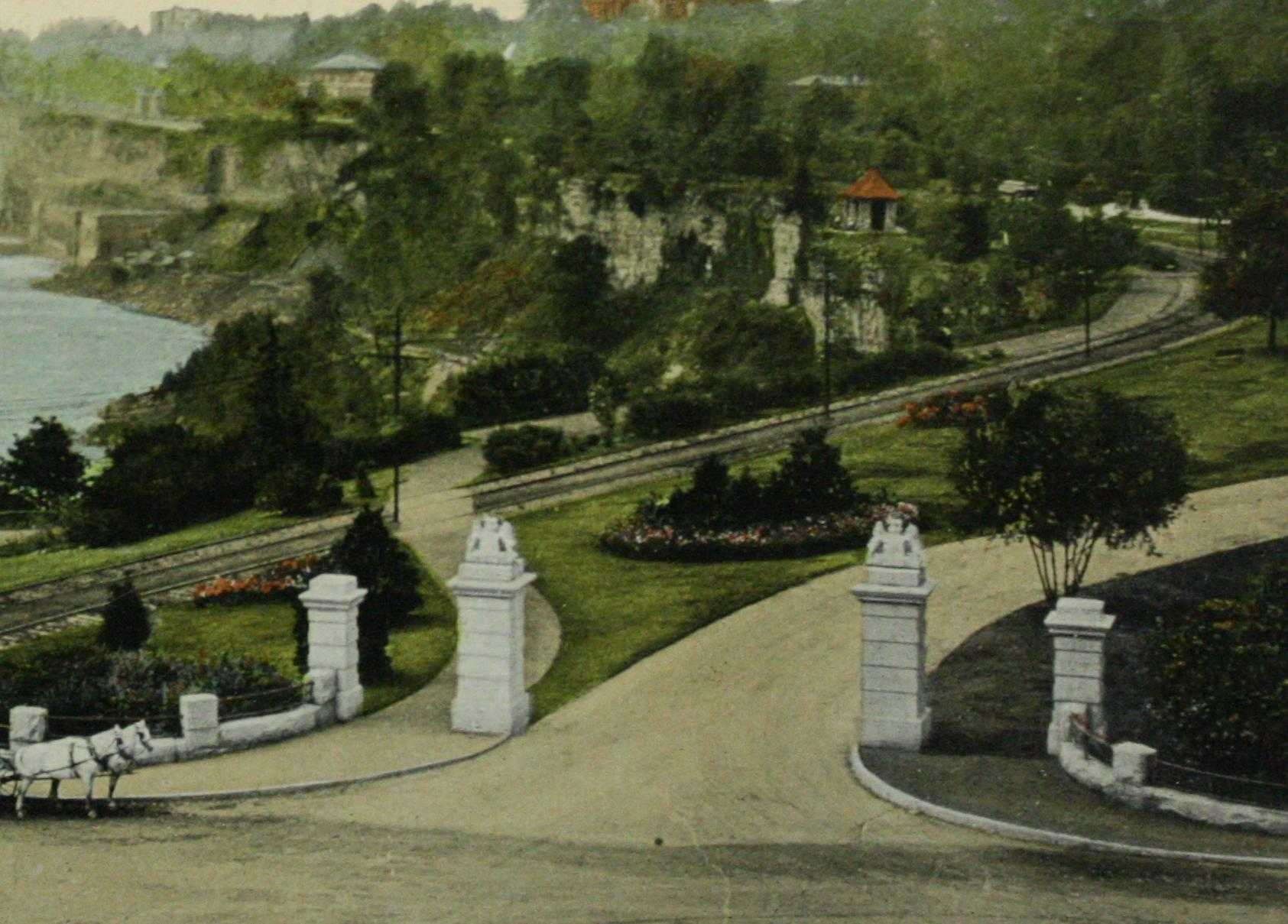 Mowat Gate at the entrance of Victoria Park. Colourised photo of the Victoria park, located on today's Clifton Hill. Horse and buggy appear at far left of the image; two white, stone columns mark the entrance to the Park, atop these stand the shields of Canada. A train track reaches around the outside of the park and a pathway leads down the Parkway to the Falls, which is located off shot to the left. A power station is visitble atop Murray Hill and the out-flows into the River below. A small building, possibly rambler's rest, is midway between the camera and the Falls. Trees dot the foreground but many appear in the background. There are gardens with small shrubs and beds of flowers in the foreground in the park.