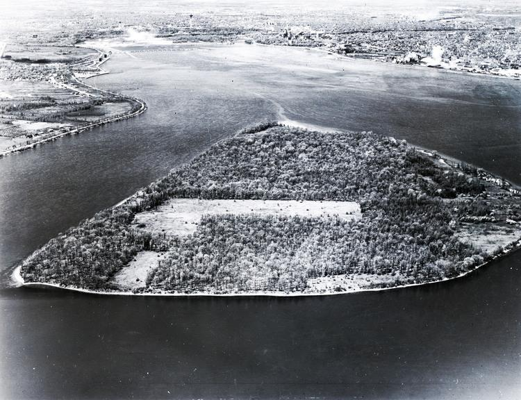Image courtesy of the Niagara Falls (Ontario) Public Library. Navy Island, large island situated in the Niagara River, slightly toward the Canadian side. Black and white photograph, island is covered with trees aside from two patches which have been cleared; the largest is at the middle of the island and has an addition to the bottom. The second clear cut area is below the largest one and connects to the up-stream river. The mist and Falls are in the background. The left side's river is very straight while the right side's river is curved. Canada is to the left of the island; U.S. to the right.