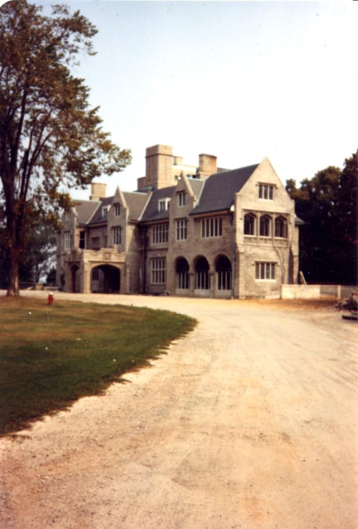 Image courtesy of the Niagara Falls (Ontario) Public Library. Colour photograph, laneway leading up to a large stone, gable-ended mansion (Oak Hall). Several fireplaces are situated around the home denoting wealth as these would have to be constantly filled and refilled with wood or coal, requires material and staff to do so. Many windows dot the structure as well, there is no particular pattern to the installation of the windows. A covered entrance way at the middle of the building.