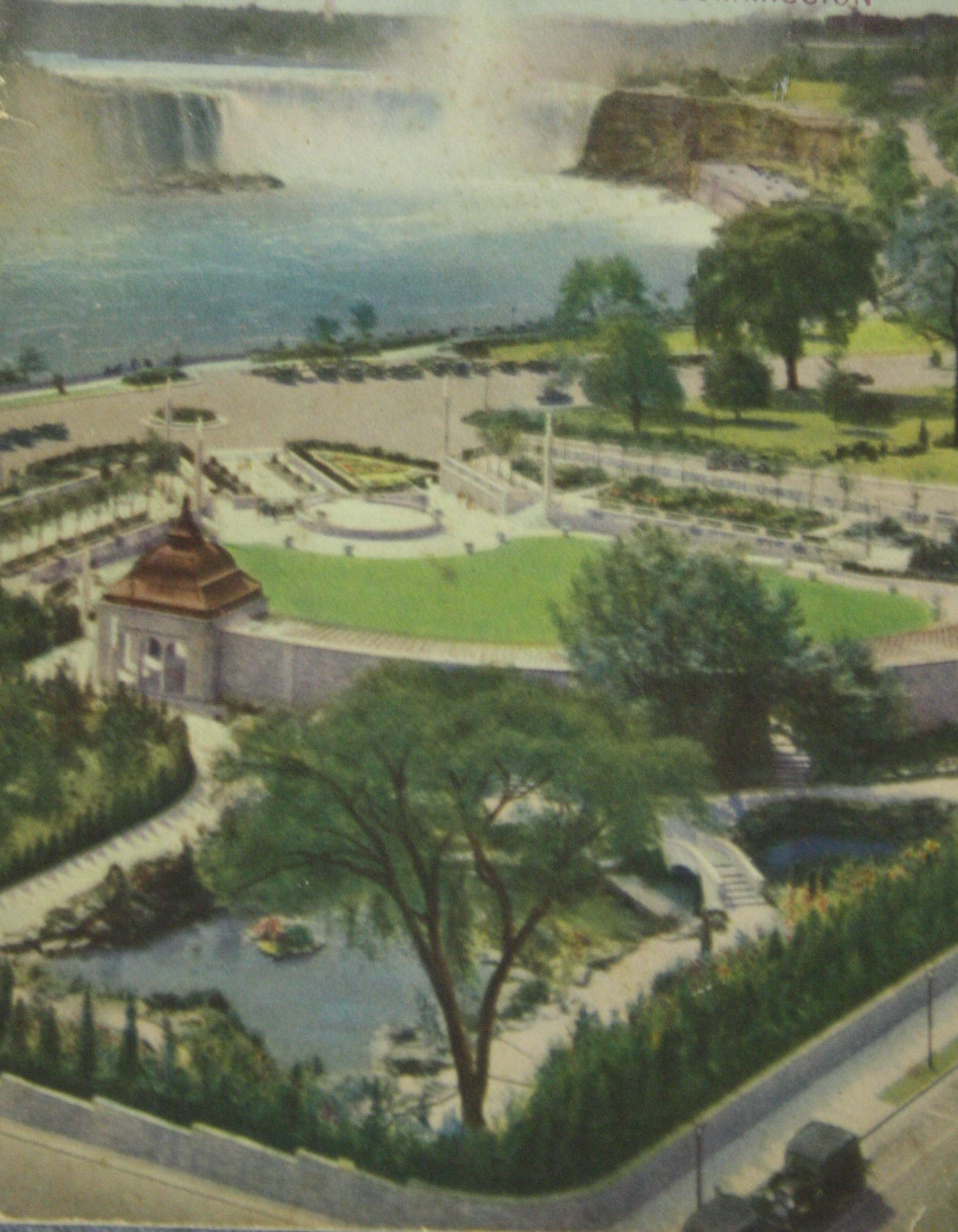 Photograph of the Oakes Garden Theatre. Starting in the background, there is the Horseshoe Falls with blue water flowing over and mist rising. The Niagara Parkway, road, is in the mid-ground with the intersection at the bottom of Clifton Hill and several trees. Well-cultivated gardens flow to this intersection from the Theatre side, also a large lawn framed by concrete stairways, walkway and a wall separating the theatre area from the reflection natural area just behind the wall. Falls Avenue is in the extreme foreground with a couple of black cars and telephone or light poles.