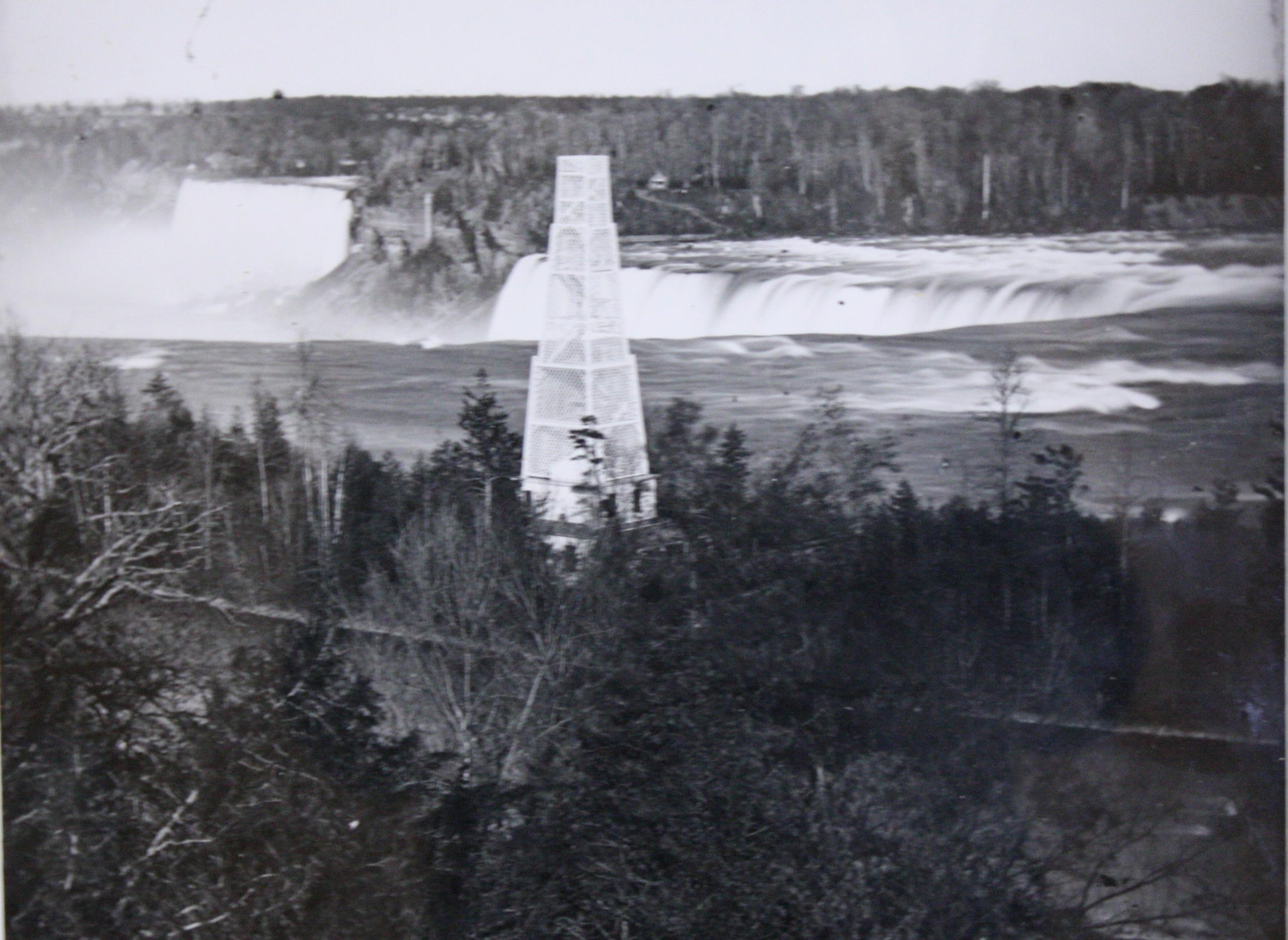 Street's Pagoda. Latticed tower allowing a view of the Niagara Falls. Many trees surround the structure. It is stark white in contrast to the darkness of the trees and water. The stair-case which a potential viewer would walk up appears through the lattice. American Falls is at far left, the Horseshoe Falls is directly behind the tower.