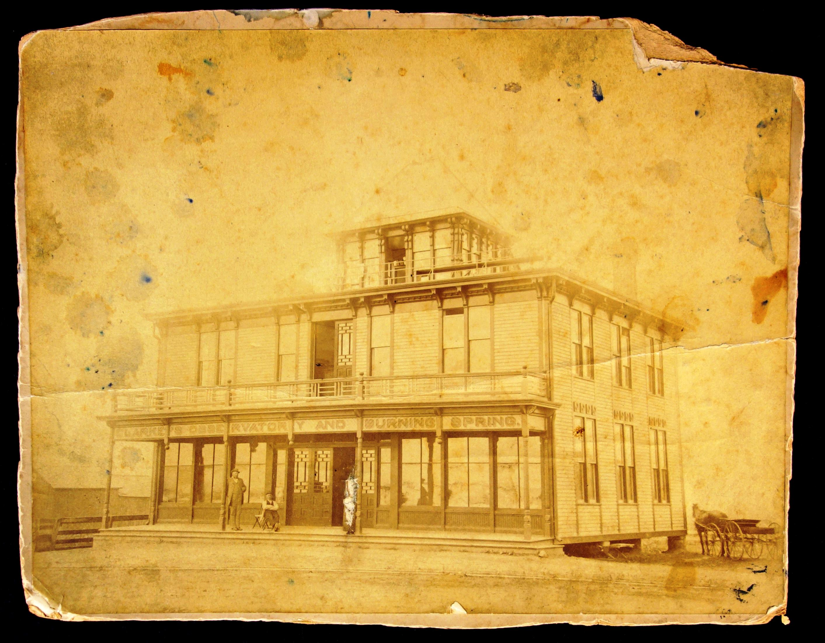 Clarke's Observatory and Burning Spring. Sepia toned image with an Italiante featured three-storey building, three men standing in the front, one has been scratched out via trauma. The image is in poor condition, tattered edges and spots.  There is a porch which surrounds the ground floor front. The doors have intricate patterns. The second  story has a veranda with windows and a door with the same design. The third level is a cupola from which the observing of the Niagara River can occur.