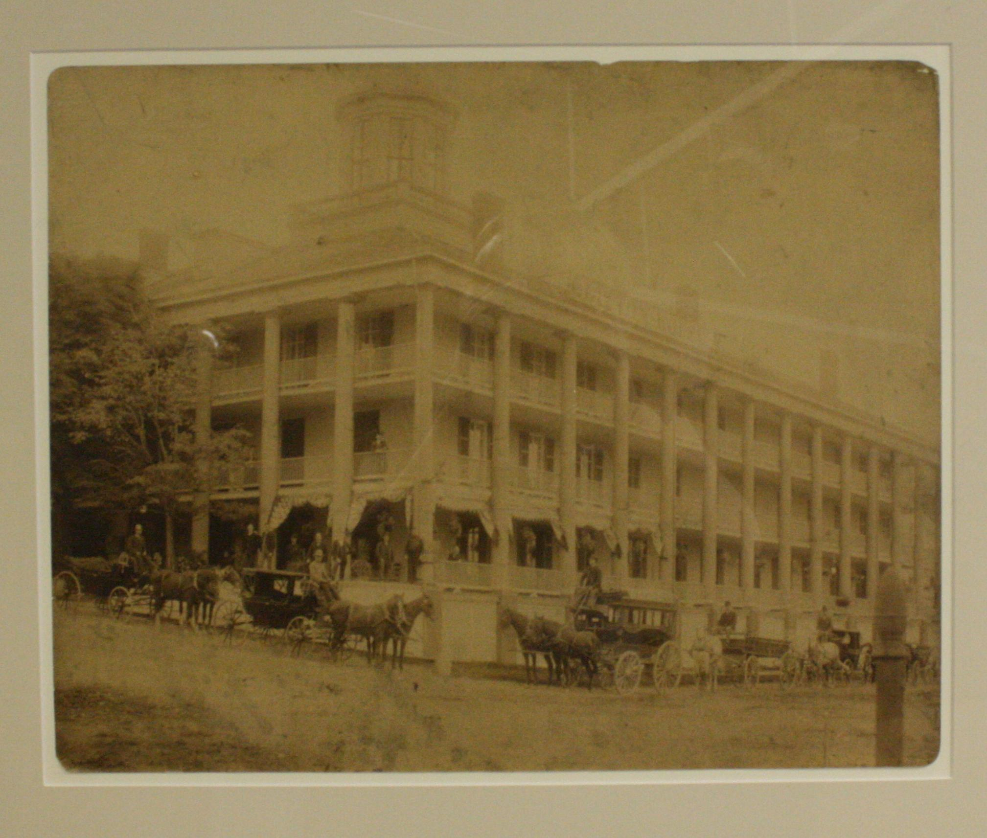 The first Clifton Hotel. Sepia tone small square photograph of the First Clifton Hotel , the photo has rounded corners. Large, popular hotel with many hourses and carriages in the froung along Clifton Hill and Niagara Parkway. There is one tree at far left, four-stroey buildings with columns running between each balcony and laticed bannisters. The roof has a cupola on top.