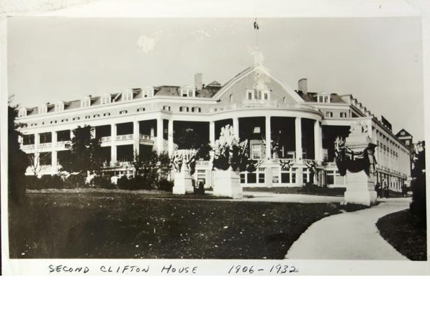 The second Clifton House. Black and white image of the Second Clifton Hotel. Large garden in the front of the building, pathway connecting the roads to the  front of the Hotel. The front is a large open bay with columns which denote a classical structure. The open balconies of the First Clifton Hotel are restricted and the third storey is closed except for the dormers in the mansard roof. The front door has a large balcony over it and a gable. At the bottom of the photograph is hand-written Second Clifton House 1906-1932.