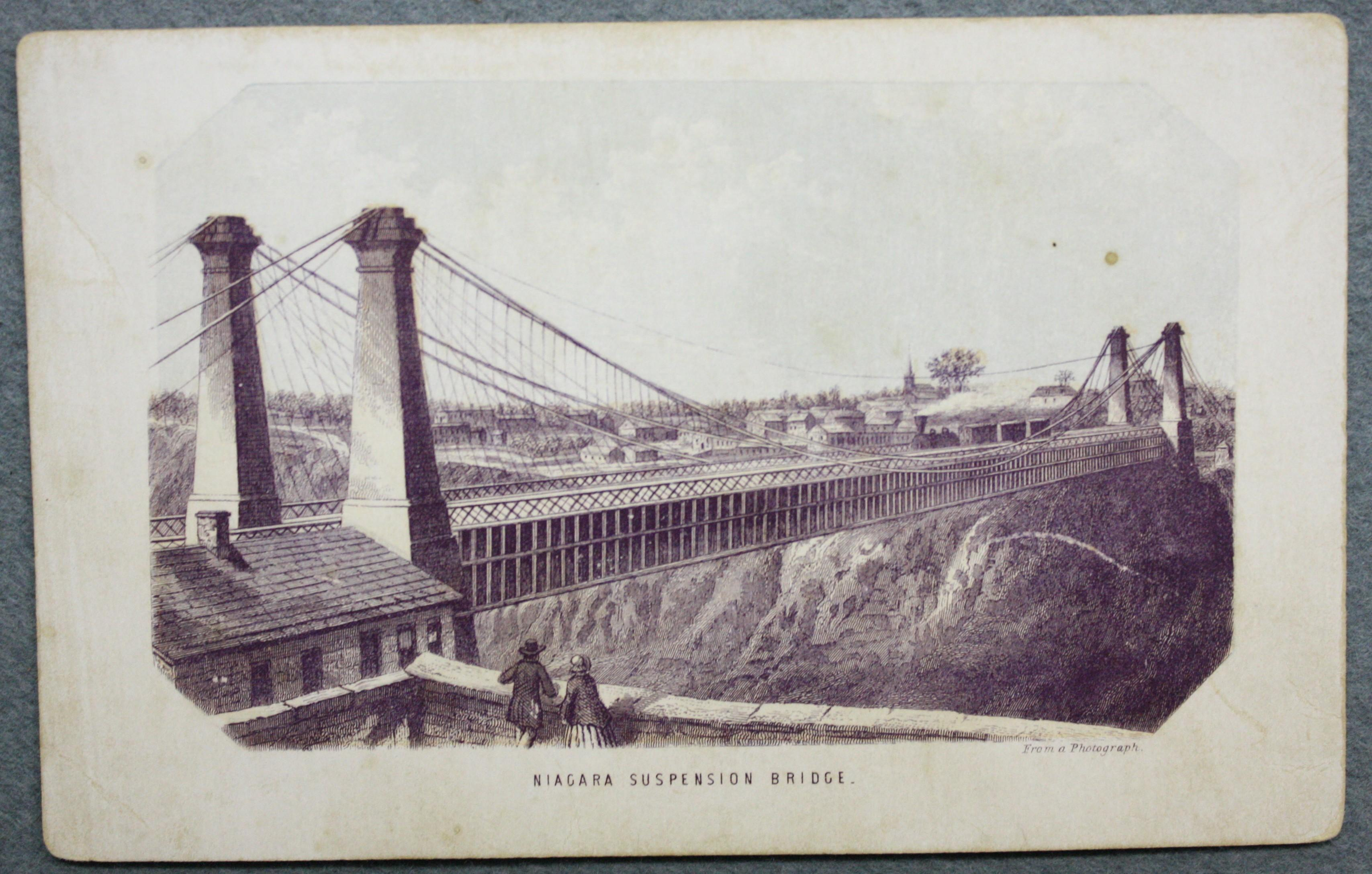 Photograph on heavy card of the Railyway Suspension Bridge. Four stone pyolons form the main supports for  the suspension cables. They taper as they go up, then flair out slightly at the cap. thick cables stretch from beyond the bridge to the left to anchor points beyond the bridge. Then up to the pylons and sink down to the middle of the bridge where they swoop back up to rejoin the next pair of pylons and then back down on the US side. A wooden structure makes the bridge top and incasing for the roadway structure beneath the railway top. A single train is on the top of the bridge with three cars and smoke trailing from the engine. A stone building is in the foreground with two people stnaidng next to it. There is a shingled roof and a chimney at the centre of the of the building. In the far background there are many buildings standing in what should be Niagara Falls New York.