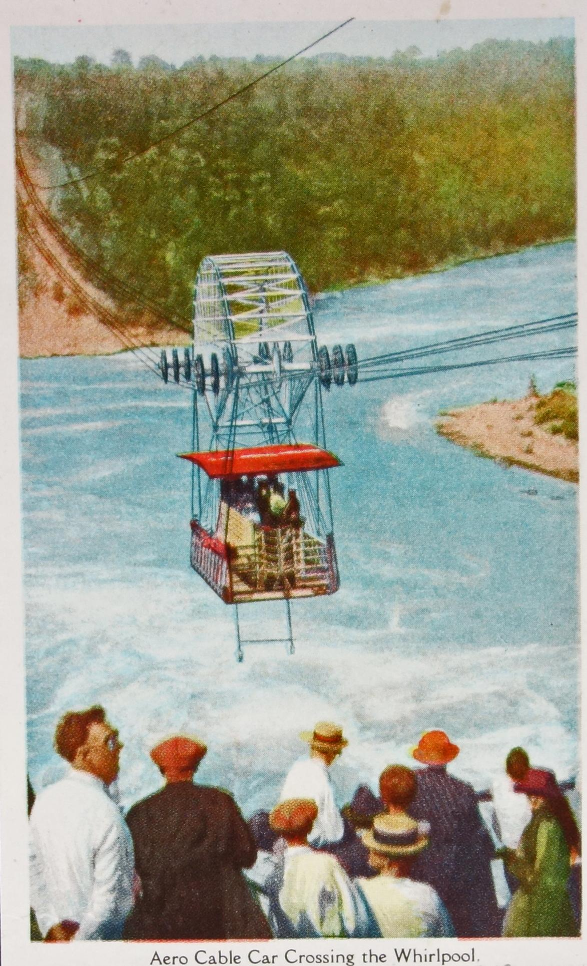 Aero Car crossing the Niagara Whirlpool Rapids. Colourised photograph with people waiting to get on the Spanish Aero Car which travels across the Whirlpool. A dozen people are in the near fore-ground while the Aero Car travels moves around the middle of the gorge. There are people on board the Aeor Car already, huddled in the middle of the car. The cables which span the gorege are drooping under the weight of the Aero Car. Large wheels of the car connect to the cable to provide sfe transit across the Whirlpool. The Aero Car is bright red. The churning water below is mostly white with a bit of blue and the ground around the River is rocky.   At the bottom of the image is typed