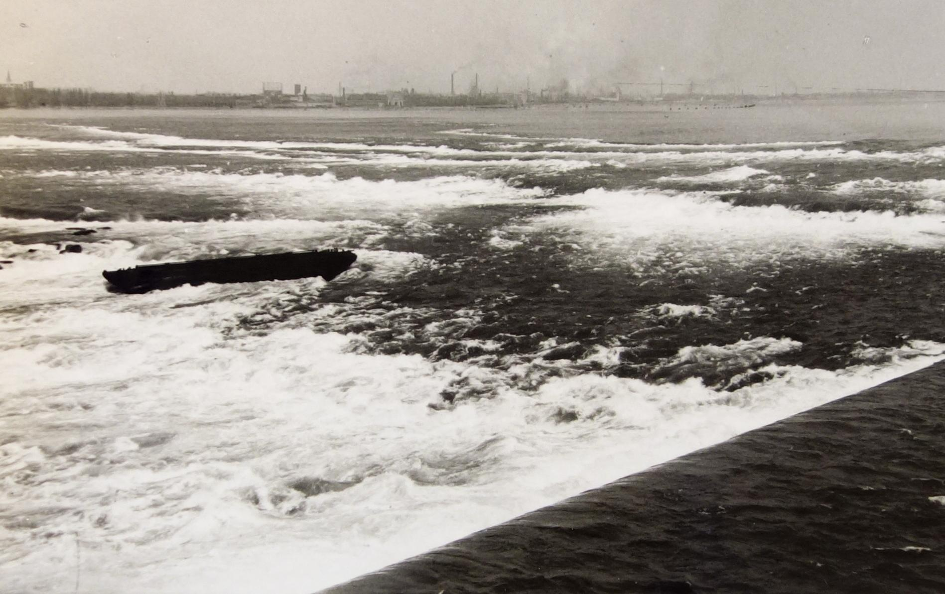 Black and white photograph of the Scow, a barge, in the middle of the River above the Falls. White water rapids surround the Scow as the water hits of the rocks which surround it in  the lead up to the Falls. The industry of Niagara Falls New York appears in the background. The Scow is very dark and showing signs of wear in the image with a couple of pieces missing.
