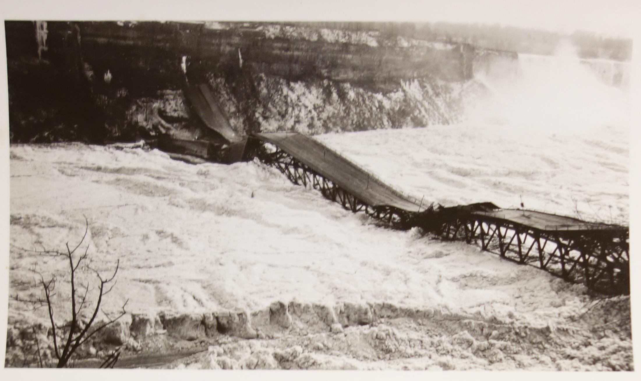 Collapse of the Upper Steel Arch Bridge on January 27, 1938. Black and white photograph of the wreckage after the ice jam pushed the arch bridge off of its footings. The dark steel structure juxtaposes the white ice and snow. The American Falls is at the far right and thus the photo is taken from the Canadian side. A tree is in the fore-ground at the left of the image with no leaves.