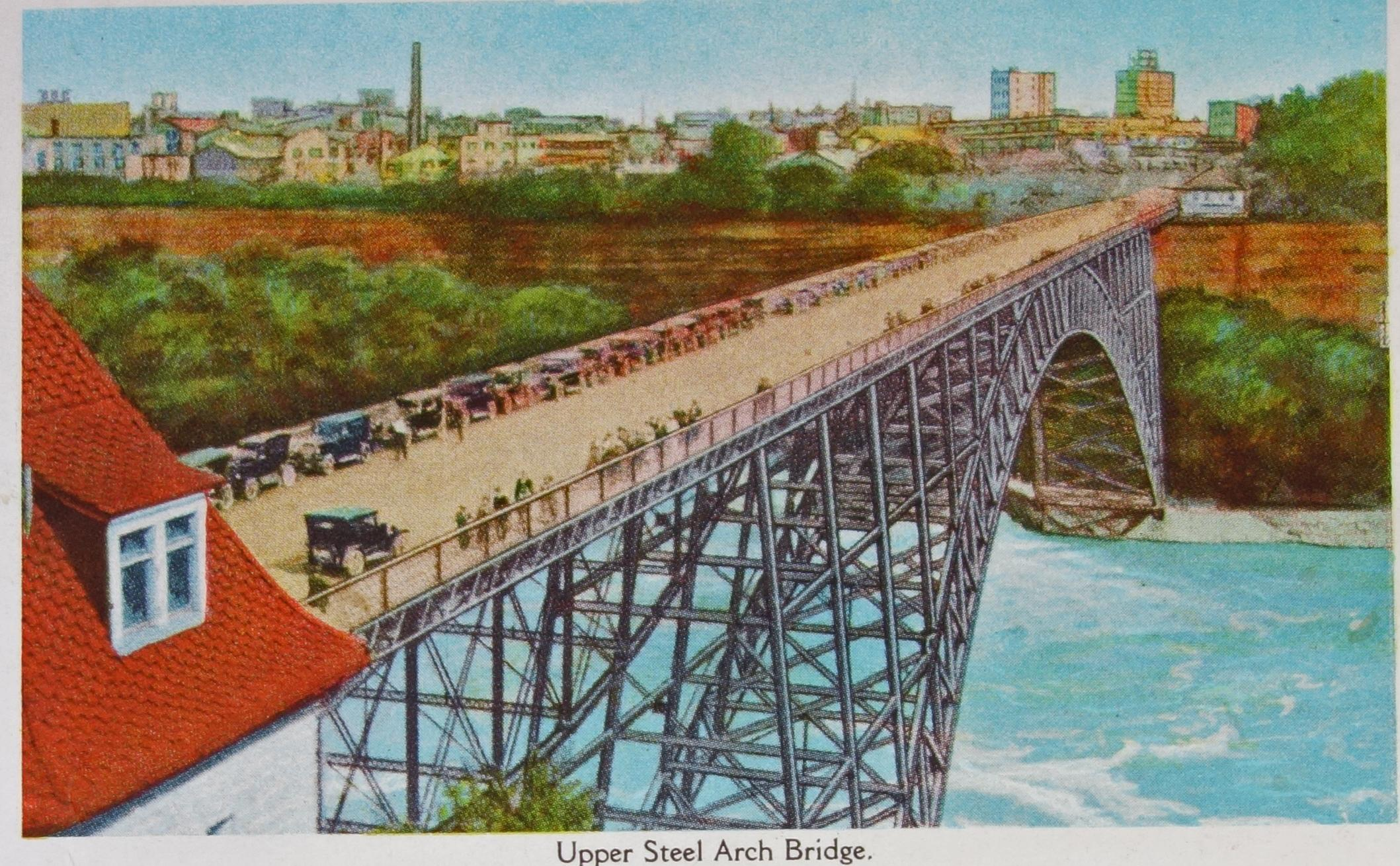 The Upper Steel Arch Bridge or the Honeymoon Bridge. Colourised photograph of the Honeymoon Bridge from the Canadian side. The 1929 Art Deco, Niagara United Office Building appears in the background in Niagara Falls New York State. Many cars are lined along the wooden topped bridge and on the near side (the south side) to have a view of the Niagara Falls. The feet of the arch bridge are barely above the water line. A red-shingle-roof building is in the extreme fore-ground and to the left of the creator. The trestling of the steel is noticeable, as is the swooping braces at the beginning before the main arch of the structure.