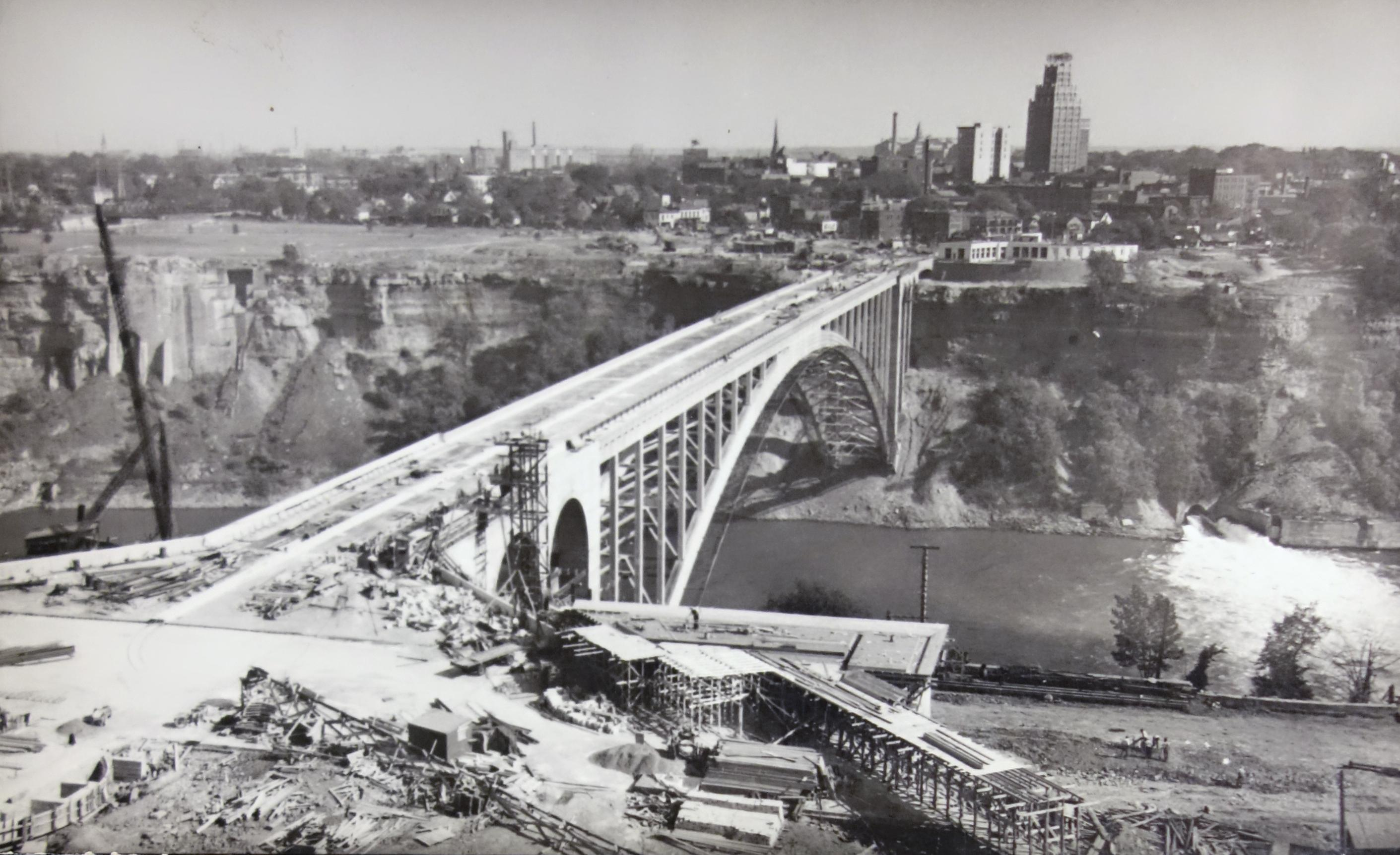Construction of the Rainbow Bridge. Photograph taken from the Canadian side looking toward the American side, the Niagara United Office Building is on the opposite shore. The former footings of the Honeymoon Bridge is at the right; the footings of the Rainbow Bridge are twice as far from the water line as the previous bridge's. The concrete portions of this bridge are the top and the arches prior to the steel riveted main arch, which forms the majority of the bridge. Several trees dot the sides of the gorge on both sides. There are no workers in this image.