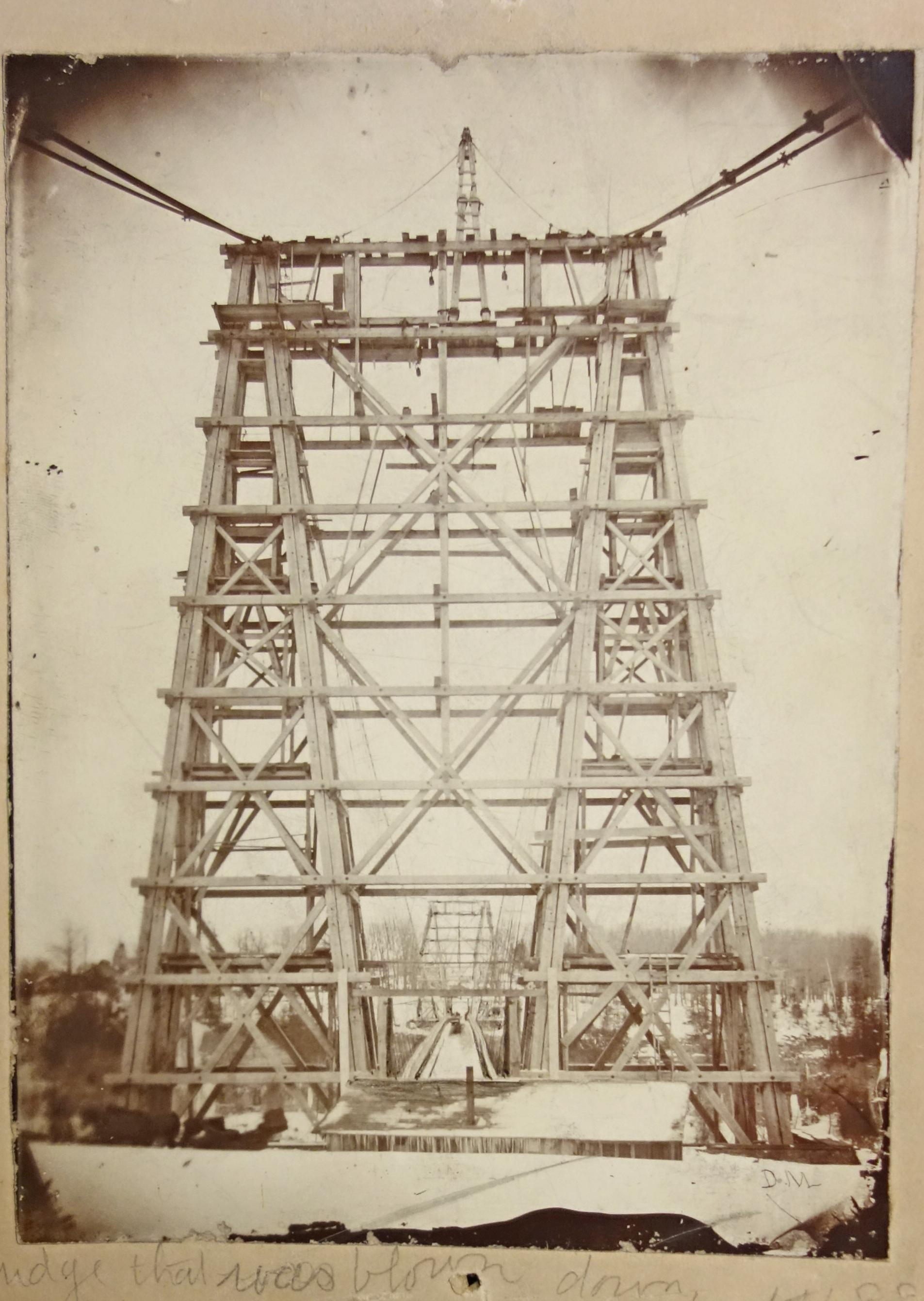 Photograph of the First Falls View Suspension Bridge, camera is pointed the length of the bridge along the deck. Imposing wooden, trestle structure of the pylons take up most of the image; the other pylon stands at the other end of the bridge. There is a building in the fore-ground infront of the bridge. Large cables hold the pylons of the bridge down which are in anchor points behind the photographer. Underneath the photograph is written