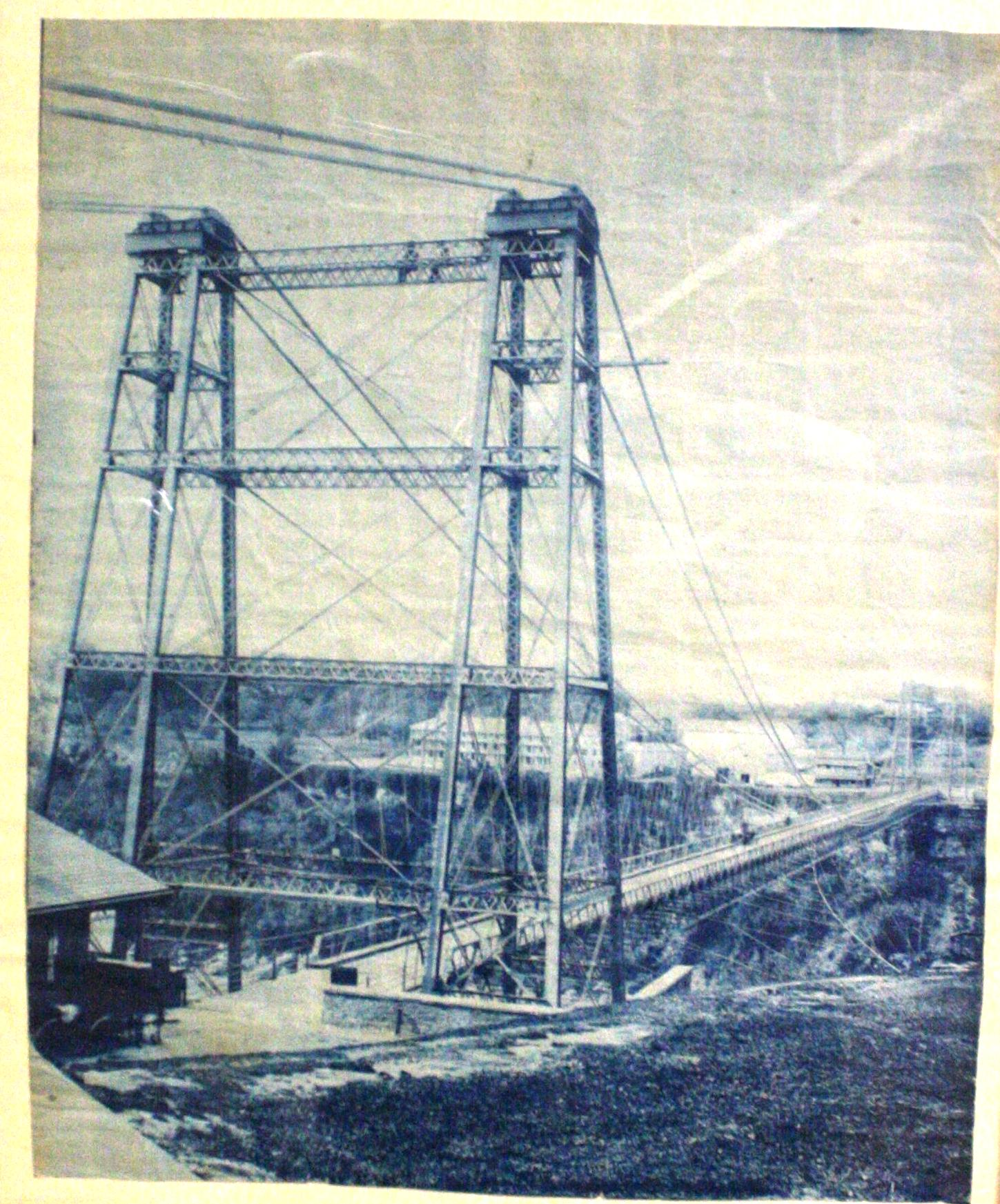 The Second Falls View Suspension Bridge (1889-1897). Black and white image of a steel towers, large cables going behind the photographer and many stretching alongside the length of the bridge to minimise the sway after the last one collapsed. The photograph is taken from essentially the same point as the updated Falls View Suspsension Bridge, with a moraine and Clifton House at the opposite side of the image, although the Clifton House is visible due to the minimal material needed in the steel towers. There is a building to the left of the bridge which could be the customs house as well as a rise to the right of the bridge. The bridge is wide enough to fit two lanes of traffic.