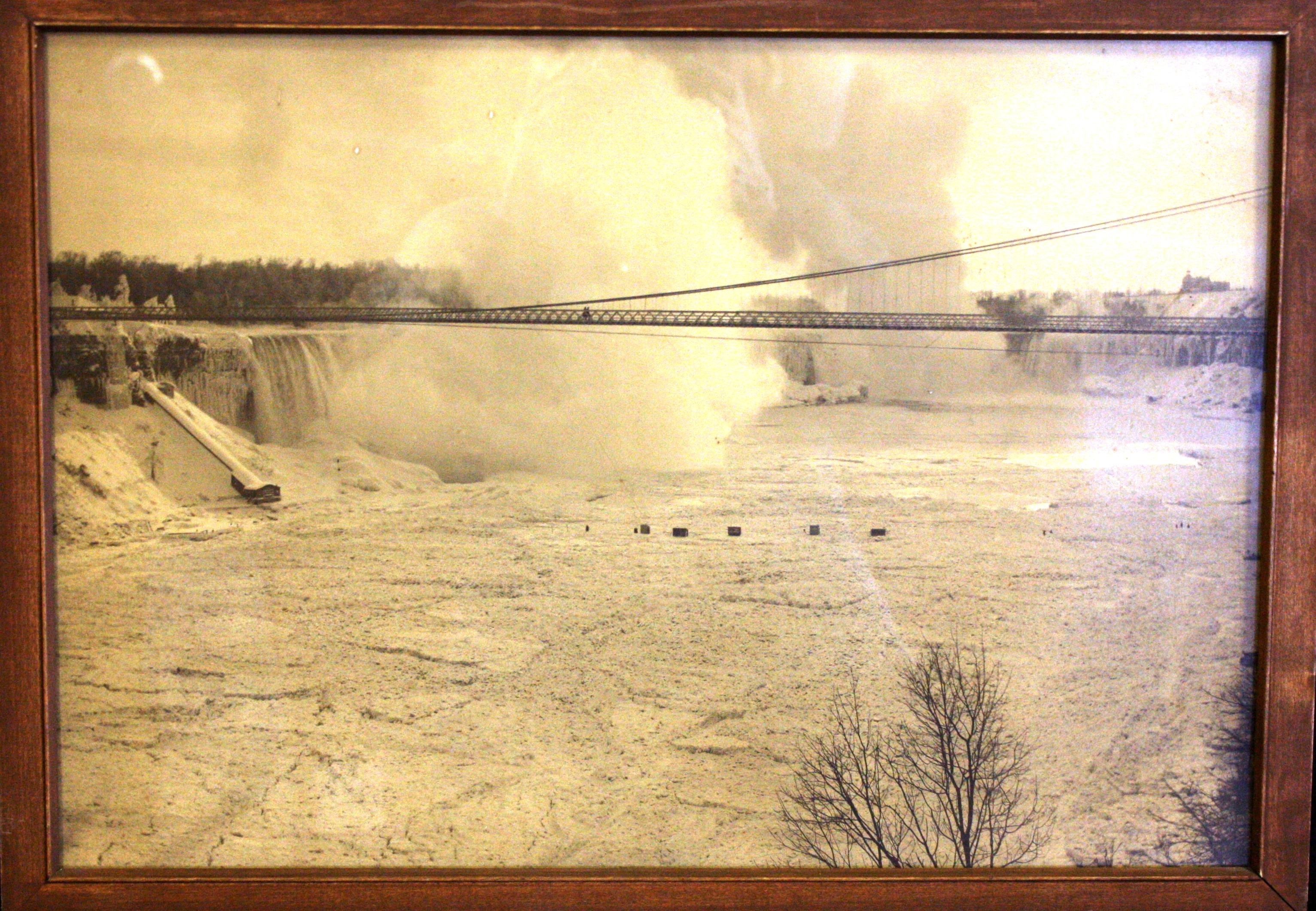 Sepia toned image of the Falls in Winter. There are structures on the ice bridge, a sheet of ice which would form during the winter, these would often be photographers. This image is take from the 1890s. The Suspension Bridge is in the foreground. The mist from the Falls is  still rising up in to the sky so the Falls were not completely stoppe as they were in 1848.